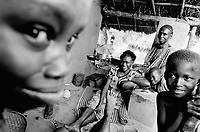 """Guinea. State of """"Guinée Forestière"""". Massakoundou. Camp for Sierra Leoneans refugees. Daily life.  Woman and her children near the kitchen space. Family seated on the ground in front of  her clay house. © 2001 Didier Ruef"""