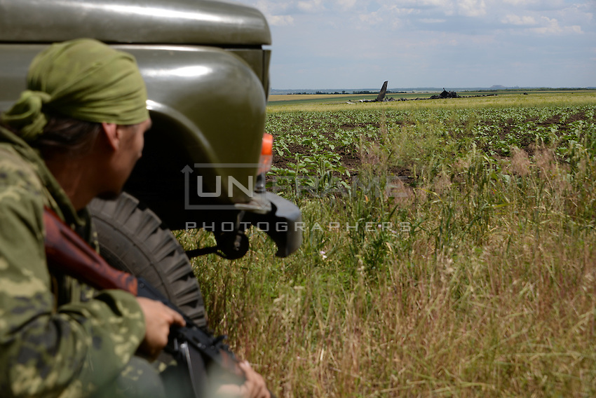 Pro-Russian militia secure the impact area of downed Ukrainian military transport plane (IL-76). Novogannivka, ( Lugansk ), Ukraine.<br /> <br /> The night before plane was shot down by anti-aircraft guns and missiles of the militia of Lugansk peoples republic causing 49 casualties between Ukriane soldiers.