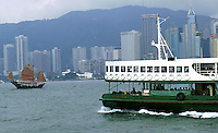 The Star Ferry and a junk cross the Victoria Habour in Hong Kong.