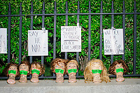 """A display of protest signs and female white mannequin heads with tape over the mouths are seen against a fence as thousands gathered outside the Massachusetts State House in Boston, Massachusetts, on Sun., May 31, 2020, to demonstrate against police brutality after the killing by police of George Floyd in Minneapolis, Minnesota, the previous week. Protests, sometimes violent, have erupted around the United States. This protest was organized by an organization called Black Boston. Protesters often chanted """"Black Lives Matter"""" and """"Fuck the police."""" The protest began at 6:30pm in various parts of the city, and around 9pm, after most protesters had left, there began to be clashes between people and police, especially in the Downtown Crossing area of Boston and around Boston Common.  The protest signs here feature hashtags and read """"Say her name,"""" """"White Silence is Violence / Black Lives Matter,"""" and """"Justice for George Floyd / Breanna Taylor."""" Names of women of color who have been killed, including by police, are written on the tape on the heads' mouths including Breonna Taylor, Frankie Ann Perkins, Mya Hall, Latasha Harlins, and others."""