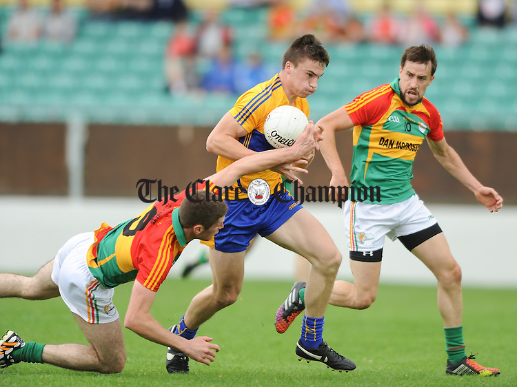 Jamie Malone of Clare in action against Hugh Gahan and Michael Meaney of Carlow during their All-Ireland senior championship round 2B game at Dr. Cullen park. Photograph by John Kelly.