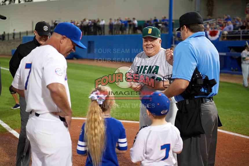 Siena Saints head coach Tony Rossi (40) during the lineup exchange with Florida Gators head coach Kevin O'Sullivan (7) and home plate umpire Josh Miller (right) before a game on February 16, 2018 at Alfred A. McKethan Stadium in Gainesville, Florida.  First base umpire Chris Tipton is to the left.  Florida defeated Siena 7-1.  (Mike Janes/Four Seam Images)