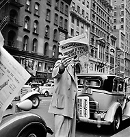 Street Corner Saint: Social Justice newspaper, founded by Father Coughlin, sold on important street corners and intersections in New York City. 1939.<br /> <br /> Photo by Dorothea Lange.