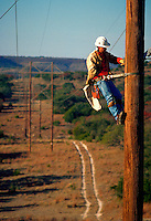 A utility worker on a pole.