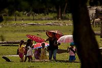 Crianças vão a escola acompanhada pela professora e se protegem do sol com sombrinhas.<br /> <br /> Com a força das águas, aliada ao fenômeno da Pororoca na foz do Amazonas, toras de madeira são jogadas na beira da vila Limão. A região das ilhas Cavianas, onde fica a vila,  é um dos últimos pedaços de terra no rio Amazonas em seu encontro com o  Atlântico.<br /> Marajó, Chaves, ilhas Caviana, Pará, Brasil.<br /> 17/06/2011<br /> Foto Paulo Santos