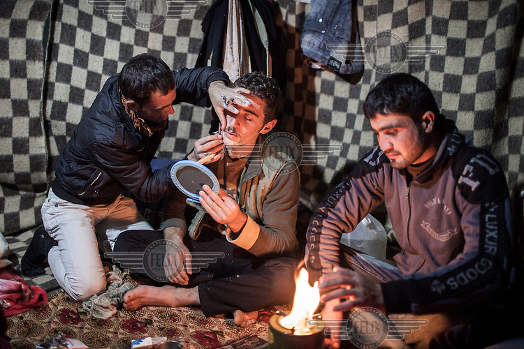 Rakan Ahmad (24), who defected from the Syrian army several months before, shaves his friend's beard while Abdul Baset, another Syrian army defector, warms himself by a small parafin stove. The 3 men are Kurdish Syrian refugees living in an unfinished mosque in the Domiz refugee camp in Northern Iraq.