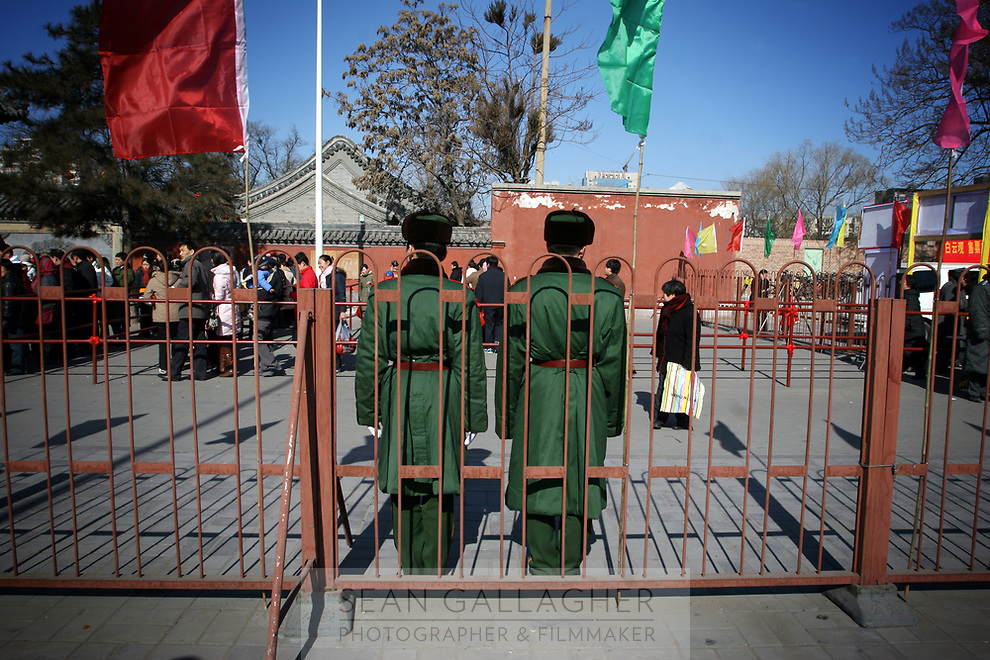 CHINA. Soldiers watching worshippers during Chinese New Year in Baiyun Temple in Beijing.  Chinese New Year, or Spring Festival, is the most important festival and holiday in the Chinese calendar In mainland China, many people use this holiday to visit family and friends and also visit local temples to offer prayers to their ancestors. The roots of Chinese New Year lie in combined influences from Buddhism, Taoism, Confucianism, and folk religions.  2008