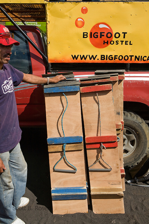 Employee of Bigfoot Hostel stands next to volcano boards, which are leaning against a pick-up truck at Cerro Negro volcano, Nicaragua