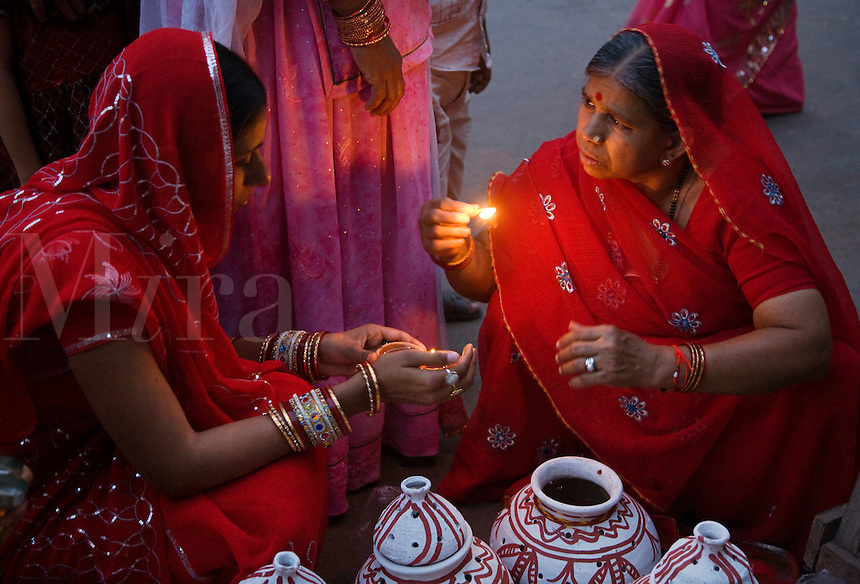 Rajasthani women place a candle in a clay pot as part of the GANGUR FESTIVAL in JOHDPUR - RAJASTHAN, INDIA