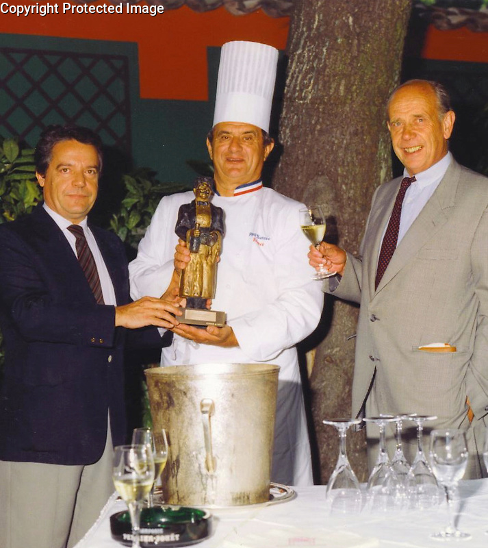 """Guy Buffet, Chef Paul Bocuse and President of Champagne Perrier Jouet, Pierre Ernst, presenting Guy's """"Gaston"""" award to the Chef!<br /> c. 1987"""