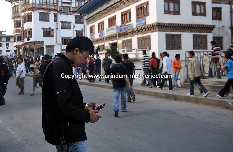 A modern Bhutanese boy wearin western clothes surfs through his mobile at Thimpu market. Arindam Mukherjee..