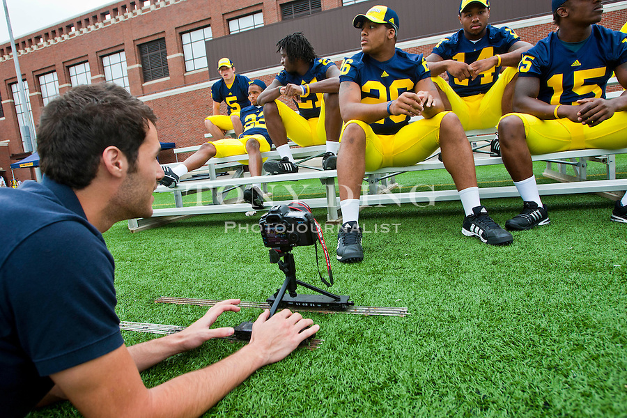 Michigan Daily photographer Sam Wolson operates a camera rolling on toy train tracks to capture video of Michigan football players at the annual NCAA college football media day, Sunday, Aug. 22, 2010, in Ann Arbor, Mich. (AP Photo/Tony Ding)