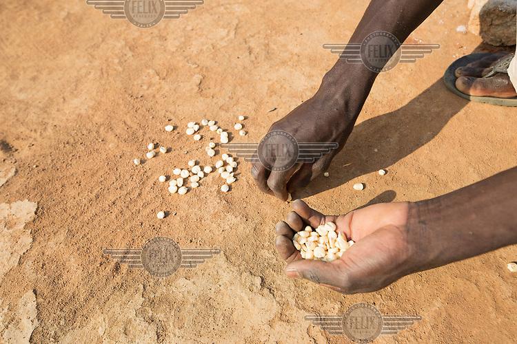 A man picks spilled maize off the ground.