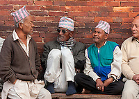 Nepal, Patan.  Men Wearing Traditional Hats Sitting on a Bench by the Royal Palace, Durbar Square.