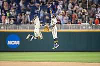 Michigan Wolverines shortstop Jack Blomgren (2) celebrates with teammate Christian Bullock (5) after defeating the Vanderbilt Commodores in Game 1 of the NCAA College World Series Finals on June 24, 2019 at TD Ameritrade Park in Omaha, Nebraska. Michigan defeated Vanderbilt 7-4. (Andrew Woolley/Four Seam Images)