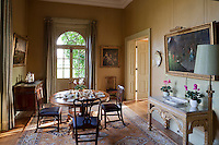 A cheerful breakfast room painted in yellow ochre