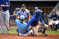 Pitcher Kyle McKenzie (27) shows umpire Joe George the ball after tagging out Anthony Alford (10) sliding into home during a game between the Dunedin Blue Jays and Charlotte Stone Crabs on July 26, 2015 at Charlotte Sports Park in Port Charlotte, Florida.  Charlotte defeated Dunedin 2-1 in ten innings.  (Mike Janes/Four Seam Images)