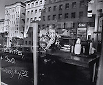 A woman takes a drag off her cigarette while eating lunch at a café in the heart of the tenderloin district of San Francisco, California.