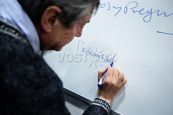 Madrid, Spain, February 12, 2015. A member of the left wing [party] Podemos writes on a blackboard before their weekly meeting in Salamanca's neighbourhood in Madrid.