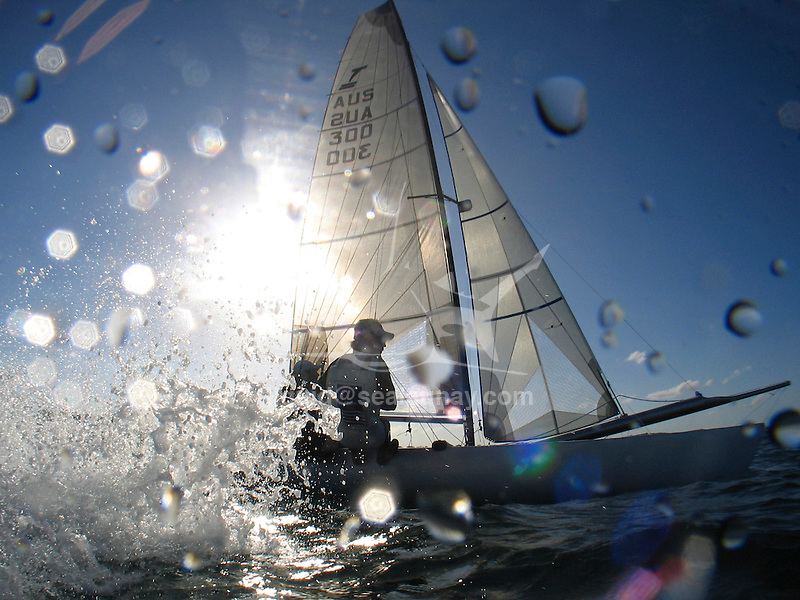 """A Tornado with the skipper Andrew Macpherson and crew Euan McNicol during a training session, Sydney Harbour..The Tornado is an olympic class sailing catamaran, with a crew of two. It was in the Olympic Games from 1976 through 2008, when multihulls were deselected for the 2012 games. It was designed in 1967 by Rodney March of Brightlingsea, England, with help from Terry Pierce, and Reg White, specifically for the purpose of becoming the Olympic catamaran. To increase its performance even further, the Tornado was modified in 2000, with a new sail-plan which included a Spinnaker and Spinnaker boom, as well as an increased sail area of the existing sails. An additional trapeze was also added, and the jib was made self tacking..The Tornado typically flies one of its two hulls; the crew balancing the boat with their own weight and by controlling the sails. With only one hull in the water, drag is significantly reduced. The Tornado also features an adjustable, rotating mast, which not only greatly improves the aerodynamics of the crucial leading edge of the sail, but also allows improved control over mast bend and thus mainsail flatness. For the high speeds and apparent wind directions seen by this high speed vessel, a flat sail profile is often required..The Tornado is said to be capable of speeds above 30 knots (56 km/h) reaching, and 18 knots (33 km/h) upwind, the Tornado class is often characterized as """"the Formula One of sailing""""."""