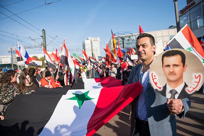 """250 bis 300 Menschen demonstrierten am Samstag den 31. Oktober 2015 in Berlin fuer die Unterstuetzung des syrischen Diktators Assad durch Russland. Sie trugen Fahnen Syriens, der ehemaligen Sowietunion, Russlands, Nordkoreas, der DDR, des Iran und Venezuelas, die sich """"alle zusammen gegen den Imperialismus zur Wehr setzen"""" wuerden. Russlands Praesident Putin wurde ausdruecklich fuer sein Militaerengagement gedankt, das Eingreifen der USA verurteilt.<br /> Im Bild: Ein Demonstrant mit einem Portraitfoto des syrischen Diktators Assad.<br /> 31.10.2015, Berlin<br /> Copyright: Christian-Ditsch.de<br /> [Inhaltsveraendernde Manipulation des Fotos nur nach ausdruecklicher Genehmigung des Fotografen. Vereinbarungen ueber Abtretung von Persoenlichkeitsrechten/Model Release der abgebildeten Person/Personen liegen nicht vor. NO MODEL RELEASE! Nur fuer Redaktionelle Zwecke. Don't publish without copyright Christian-Ditsch.de, Veroeffentlichung nur mit Fotografennennung, sowie gegen Honorar, MwSt. und Beleg. Konto: I N G - D i B a, IBAN DE58500105175400192269, BIC INGDDEFFXXX, Kontakt: post@christian-ditsch.de<br /> Bei der Bearbeitung der Dateiinformationen darf die Urheberkennzeichnung in den EXIF- und  IPTC-Daten nicht entfernt werden, diese sind in digitalen Medien nach §95c UrhG rechtlich geschuetzt. Der Urhebervermerk wird gemaess §13 UrhG verlangt.]"""