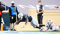 CHAPEL HILL, NC - OCTOBER 10: Javonte Williams #25 of North Carolina lunges into the end zone after being tripped by Rayshard Ashby #23 of Virginia Tech on his 19-yard touchdown run during a game between Virginia Tech and North Carolina at Kenan Memorial Stadium on October 10, 2020 in Chapel Hill, North Carolina.