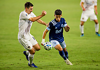 CARSON, CA - OCTOBER 18: Sacha Kljestan #16  of the Los Angeles Galaxy and Fredy Montero #12 of the Vancouver Whitecaps chase down loose ball during a game between Vancouver Whitecaps and Los Angeles Galaxy at Dignity Heath Sports Park on October 18, 2020 in Carson, California.