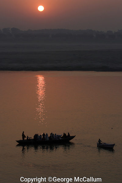 Rowing boats with tourists on Ganges river at sunset during low water season with bed of the river clearly visible Varanasi, India