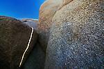 A sliver of sunlight crosses a granite boulder.