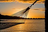 Sunset light through hammock ropes and overwater bungalows in Bora Bora, romantic honeymoon destination, near Tahiti, French Polynesia, Pacific Ocean