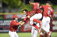 Clearwater Threshers shortstop J.P. Crawford (2) is mobbed by teammates including Corey Bass, Harold Martinez and KC Serna (8) after a game winning hit during a game against the Tampa Yankees on June 26, 2014 at Bright House Field in Clearwater, Florida.  Clearwater defeated Tampa 4-3.  (Mike Janes/Four Seam Images)