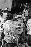 Mazatlan Mexico, young boy busking in the crowded street playing the guitar 1970s Mexican state of Sinaloa. 1973