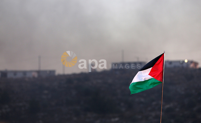 A Palestinian flag shows waveing during a night demonstration against the expansion of a Jewish settlement on the lands of Beita village, near the occupied West Bank city of Nablus, on June 21, 2021. Photo by Shadi Jarar'ah