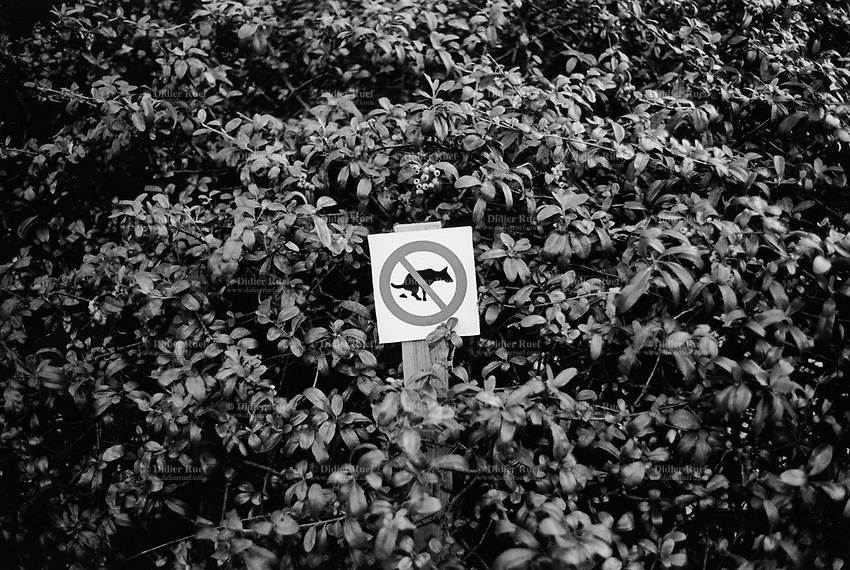 Switzerland. Canton Ticino. Lugano. A sign warns dog owners to keep dogs from pooping in the garden bushes. © 2002 Didier Ruef