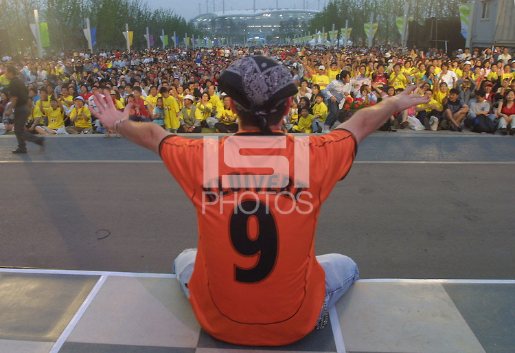 In front of a large screen set up in Seoul World Cup park for soccer fans without a ticket to watch the opening match, Scott Mathyk of Canada leads some cheers for the spectators outside of the Seoul World Cup Stadium before the opening day match between France and Senagal on Friday May 31st, 2002 in Seoul, South Korea.