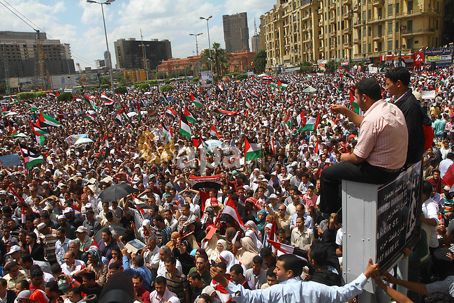 """Egyptian demonstrators wave Palestinian flags and Egyptian flags during a rally at Cairo's Tahrir Square on May 13, 2011 during a protest calling for national unity after attacks on Egyptian churches, and solidarity with the Palestinians as they mark the """"Nakba"""" or """"catastrophe"""" which befell them following Israel's establishment in 1948. Photo by Ashraf Amra"""