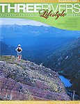 A hiker on a cliff overlooking Glacier Lake in Montana. Nelson Kenter photo used on a magazine cover