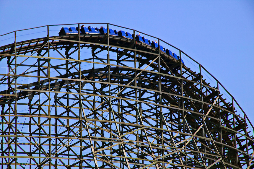 Blue roller coaster high on tracks against blue sky