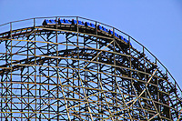 Blue roller coaster high on tracks against blue sky
