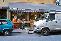 A grocery store with fruits and vegetables displayed on the pavement. A boy walking past.. Cars parked in front. Montevideo, Uruguay, South America