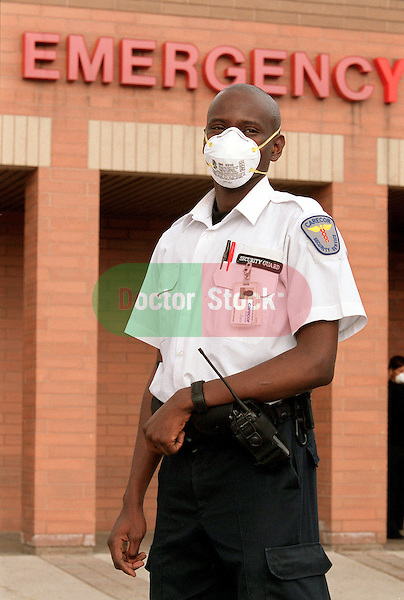 NOT MODEL RELEASED; FOR EDITORIAL USE ONLY... security guard stands watch at the hospital emergency room entrance wearing a protective mask to protect against contracting communicable illness
