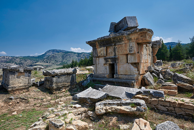 """Picture of Tomb Tomb 114 """"tomb of curses"""" of the North Necropolis. Hierapolis archaeological site near Pamukkale in Turkey.<br /> <br /> TOMB 114 (Second half of the 2nd century AD) <br /> <br /> The tomb lies on the left hand side of the road and is enclosed by a perimeter wall; it rests on a base withifiree steps, with a bench piked(1 front of it. Inside are three beds and the ossuary. On the roof, a sarcophagus, broken as result of an <br /> earthquake, bears an inscription mentioning the occupant Aelios Apollinarios and his wife Neratia Apollonis. On the facade is an inscription of great interest which refers to the punishment inflicted on those who violate the sepulchre: as well as the usual fines, it invokes diseases, misfortunes and punishments in the next world. This inscription has led to the building being named the Tomb of the Curses."""