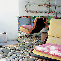 Placed in a courtyard garden on seastones is a 1960s Danish easy chair. A carefully placed mirror creates a sense of space.  A Japanese maple in a pot stands behind.
