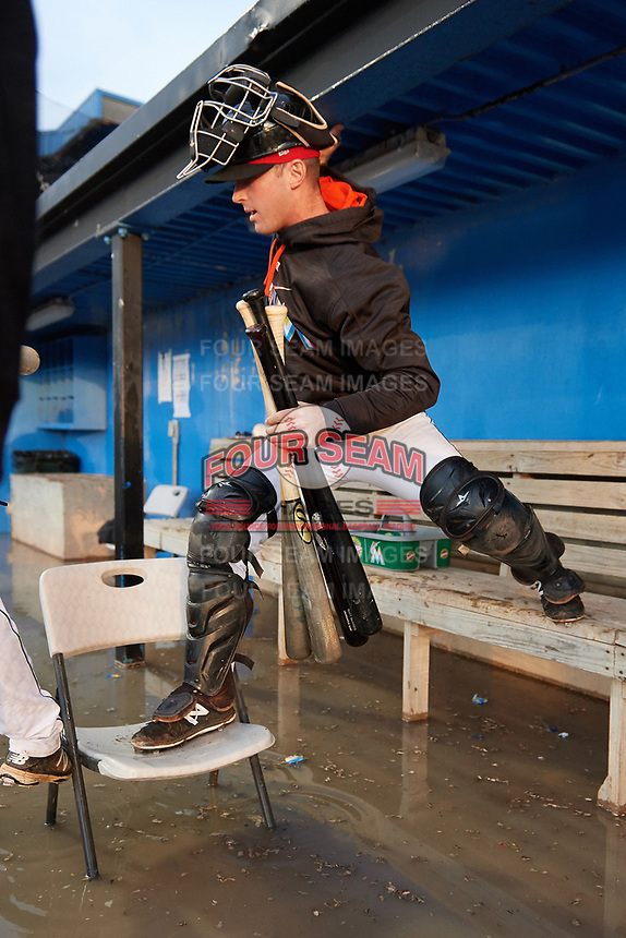 Batavia Muckdogs catcher David Gauntt (7) uses a chair as a bridge to get over the flooded dugout waters after a heavy downpour during a game against the West Virginia Black Bears on June 24, 2017 at Dwyer Stadium in Batavia, New York.  The game was suspended in the bottom of the third inning and completed on June 25th with West Virginia defeating Batavia 6-4.  (Mike Janes/Four Seam Images)