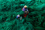 Workers pictured in a sea of nets as they look to repair them by Nguyen Sanh Quoc Huy