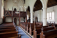 The interior of St Michael and All Angels, its rows of pews adorned with carved finials