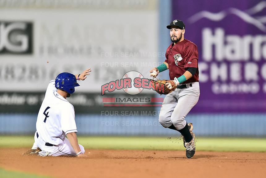 Savannah Sand Gnats shortstop Luis Guillorme (13) makes a play over a hard sliding Max White (4) during game one of the Southern Division South Atlantic League Playoffs against the Asheville Tourists on September 9, 2015 in Asheville, North Carolina. The Tourists defeated the Sand Gnats 5-1. (Tony Farlow/Four Seam Images)