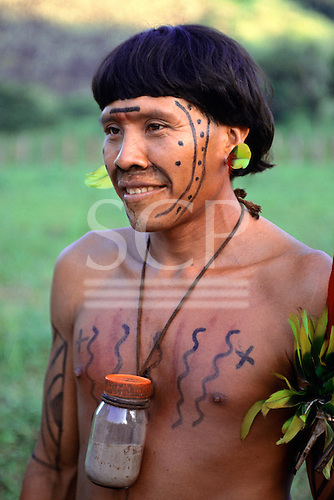 Roraima, Brazil. Levy, a Yanomami Shaman with his jar of hallucinogenic snuff, face and body paint and feather decorations.