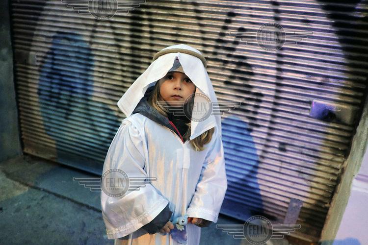 A girl dressed in thawb (thobe) watching the Zizkov Mardi Gras Parade.