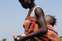 Burkina Faso, organic and fairtrade cotton, woman with her baby picking cotton by hand / Burkina Faso, Anbau von fairtrade und Biobaumwolle, Frau mit Baby bei Ernte